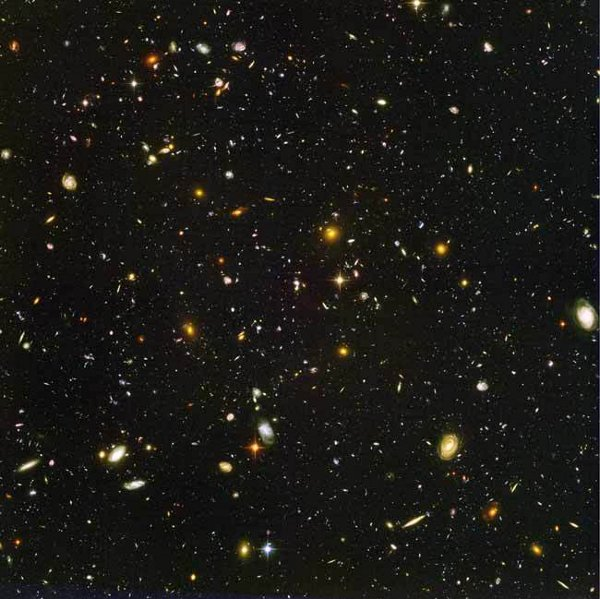 """Това изображение на десетки хиляди галактики се нарича ултрадълбоко поле на """"Хъбъл"""". Снимката включва галактики на различна възраст, с различни размери, форми и цветове. Най-малките и най-червените може да са сред най-далечните от известните днес и съществували във времената, когато Вселената е била само на 800 милиона години. Близките галактики – големи, ярки, обозначени като спирали или елиптоиди – са процъфтявали преди около 1 млрд. г., когато възрастта на Вселената е била 13 милиарда години.© NASA, ESA, and S. Beckwith (STScI) and the HUDF Team"""