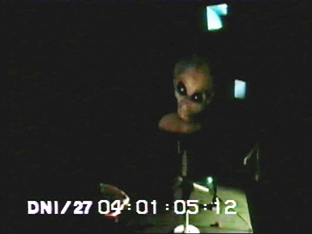 """Кадър от филма """"Зона 51"""", на който се вижда загадъчното същество с крушовидна глава и огромни, черни очи."""