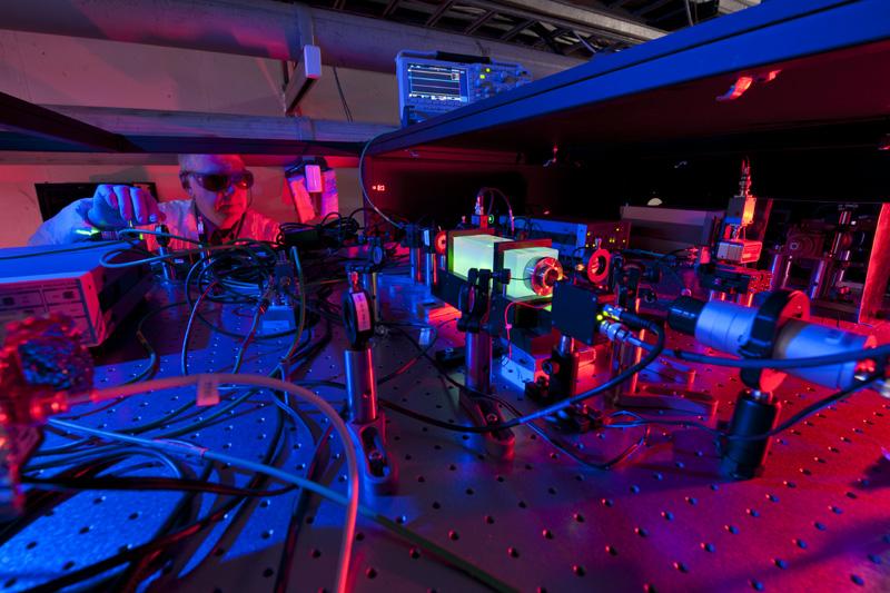 Учен от Фермилаб настройва лазерите, които са основата на експеримента Холометър. Холометърът ще използва двойка лазерни интерферометри, за да провери дали Вселената е двумерна холограма.© Fermilab