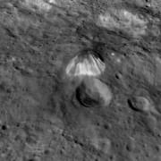 Странната планина изпъква на фона на местността със светли оттенъци и голяма височина. © NASA