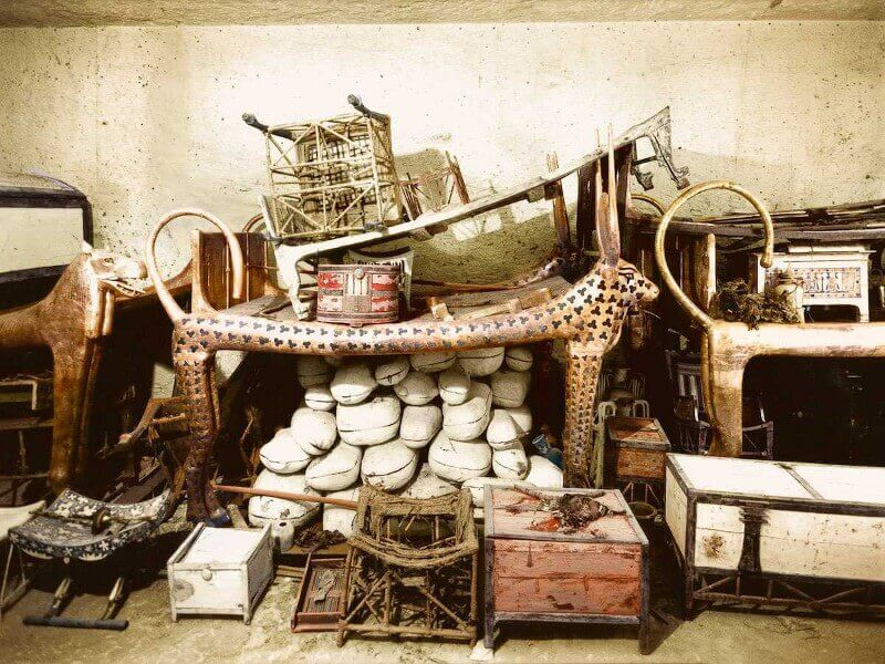 Декември 1922 г. Церемониалното ложе във формата на Небесна крава, заобиколено от запаси и други обекти в предната част на гробницата.